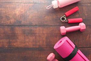 équipement de fitness rose sur fond de bois photo