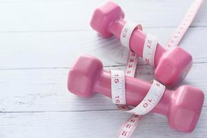 poids roses avec un ruban à mesurer autour d'eux photo