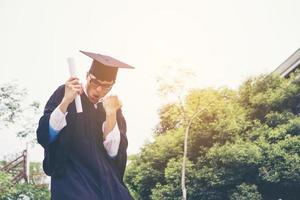 heureux étudiant diplômé tenant un diplôme en main photo