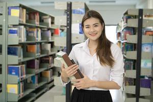 Portrait de jeune étudiant tenant des livres à la bibliothèque photo
