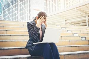 femme d'affaires a souligné tout en utilisant un ordinateur portable sur les marches photo