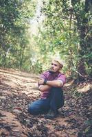 Randonneur jeune homme actif se reposer avec la nature après avoir traversé la forêt photo