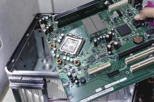 le technicien tient un ordinateur de bord pour la mise à niveau pour réparer à l'intérieur photo
