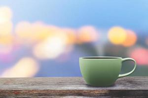 tasse à café verte sur la table avec style sombre fond bokeh