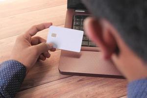 homme tenant une carte de crédit et achats en ligne photo