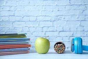 pomme et livres et crayons sur table photo