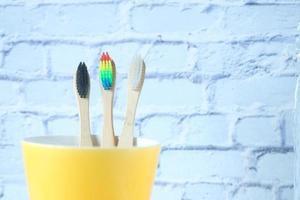 Brosses à dents colorées dans une tasse contre un mur photo