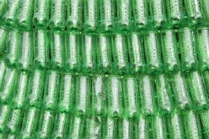 rangées de bouteilles en plastique vertes empilées les unes à côté des autres