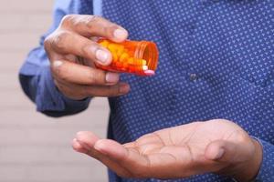 main de l'homme tenant une bouteille de pilules