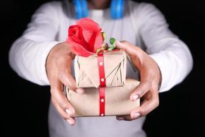 tenant une boîte-cadeau sur fond noir avec espace copie photo