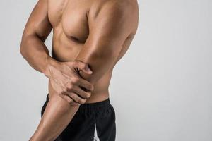 Portrait d'un homme musclé ayant des douleurs au coude isolé sur fond blanc photo