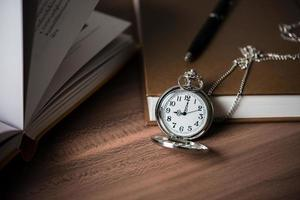 Gros plan d'une montre de poche en or s'appuyant sur une pile de livres photo