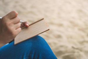main de femme écrit dans un petit cahier mémo