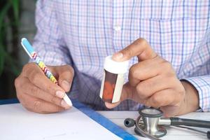 La main du médecin écrit la prescription sur le bureau photo