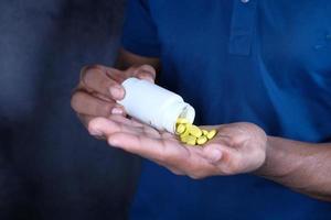 homme utilisant des pilules jaunes