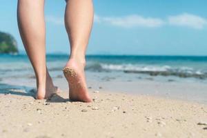 Pieds de femme marchant lentement sur une plage tropicale de sable photo
