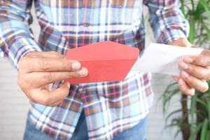 homme ouvrant une enveloppe rouge