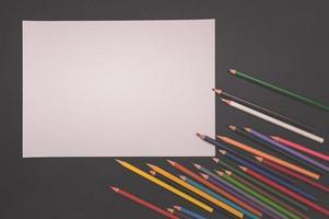 Crayons multicolores et papier blanc sur fond noir photo