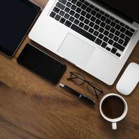 Vue de dessus de l'espace de travail avec ordinateur portable, smartphone, tablette, tasse à café, lunettes et stylo sur table en bois