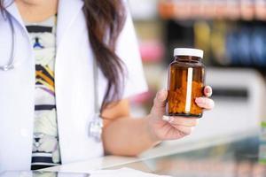 le pharmacien tient une bouteille de médicament dans la pharmacie photo
