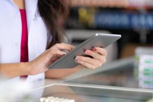pharmacienne utilise une tablette numérique dans la pharmacie photo