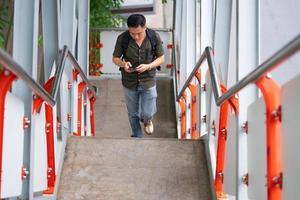 homme marchant dans les escaliers et à l'aide de smartphone en ville photo