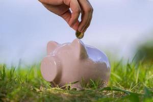 Tirelire rose sur l'herbe avec la main mettant une pièce de monnaie photo