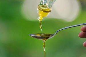 Verser de l'huile d'olive dans une cuillère sur fond de jardin parc verdoyant