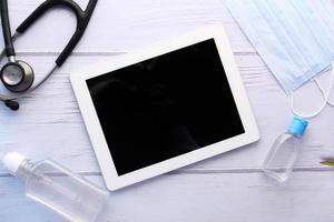 Vue de dessus de la tablette numérique, désinfectant pour les mains et stéthoscope sur table photo