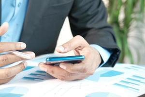 homme d & # 39; affaires à l & # 39; aide de téléphone intelligent tout en travaillant sur le bureau photo