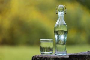 bouteille d'eau potable et verre avec fond naturel photo