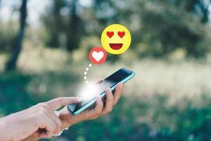 main tenant un smartphone avec des icônes de communication photo