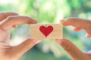 main tenant le cube en bois avec l'icône de signe de coeur avec la lumière naturelle du soleil