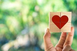 main tenant un cube en bois avec icône de signe de coeur avec la lumière du soleil de la nature