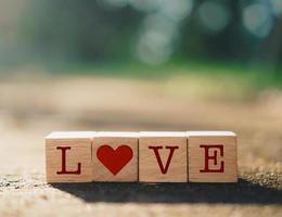 cubes en bois avec des icônes de signe de coeur avec la lumière du soleil de la nature