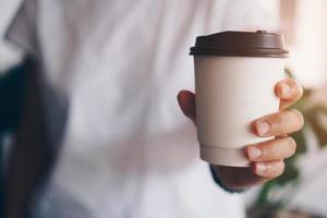 main tenant une tasse de café avec lumière du soleil