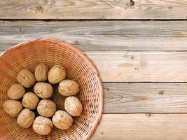 Noix entières dans un panier en osier sur fond de table en bois photo