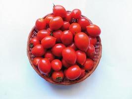 Tomates dans un panier en osier sur fond blanc photo