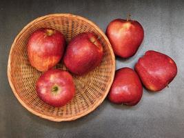 Trois pommes dans un panier en osier à côté de trois pommes sur un fond de table sombre