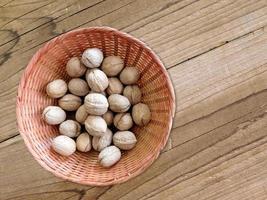 Noix entières dans un panier en osier sur un fond de table en bois photo