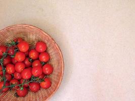 Tomates dans un panier en osier sur fond rose clair photo