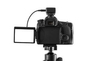 Appareil photo reflex numérique sur un trépied isolé sur fond blanc