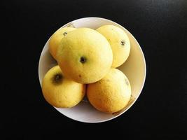Cinq pommes dans un bol blanc sur un fond de table sombre