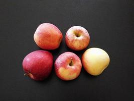 cinq pommes sur fond noir