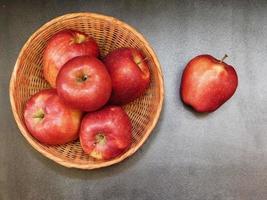 Cinq pommes dans un panier en osier à côté d'une pomme sur un fond de table sombre
