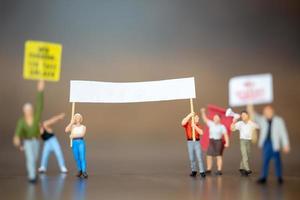 Foule miniature de manifestants levant la main et criant sur un fond en bois photo
