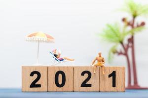 Personnes miniatures portant des maillots de bain assis sur des blocs de bois avec des numéros 2021