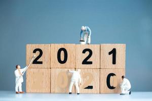 travailleurs miniatures peignant 2021 et supprimant les numéros 2020, concept de bonne année