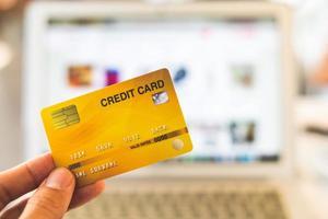 mains tenant une carte de crédit et à l & # 39; aide d & # 39; un ordinateur portable, concept de magasinage en ligne photo