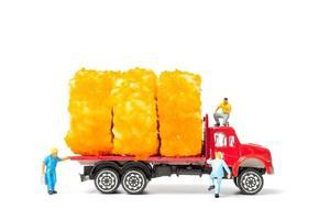 Personnes miniatures avec des rouleaux de sushi sur un camion isolé sur fond blanc, concept de livraison de nourriture